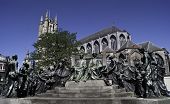 The monument is located in Ghent Belgium and depicts the van Eyck brothers: Hubert and Jan. On the background is Saint Bavo Cathedral. poster