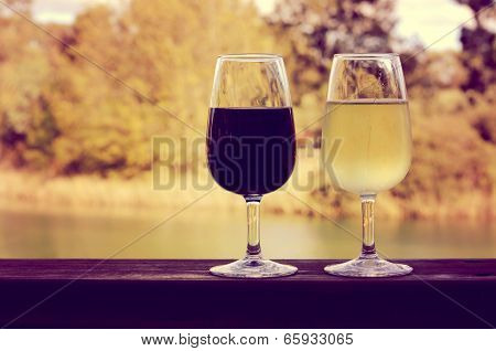 Retro Sunset Filter Style Image Of Two Glasses Of Wine, White And Red, On Wooden Rail With Country R