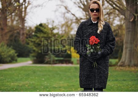 Young Female At Cemetery With Fresh Flowers