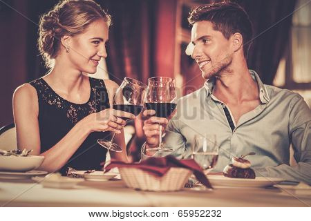 Beautiful young couple with glasses of red wine in luxury restaurant
