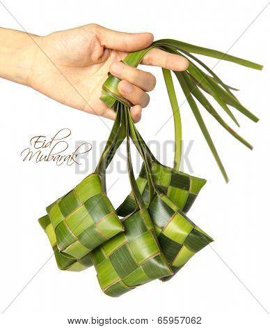 Hand Held Muslim Ketupat (Rice Dumpling) with Clipping Path. Translation: Eid Mubarak - Blessed Feast poster