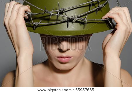 Woman Holding Hands Military Helmet With Barbed Wire