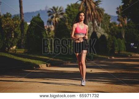 Attractive female runner in the sportswear running in the green park