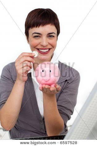Joyful Female executive saving money in a piggybank isolated on a white background poster