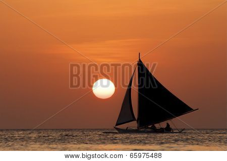 Saling into the sunset, boat at sea