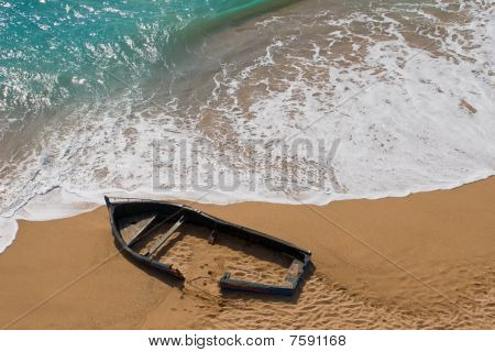 Wrecked wooden row boat in sand