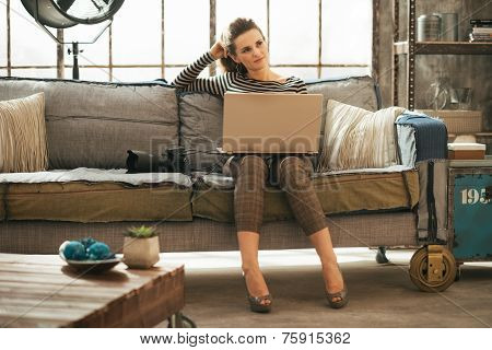 Thoughtful Young Woman With Dslr Photo Camera Using Laptop In Lo