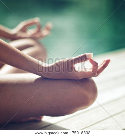 Close up Tan Woman Doing Outdoor Seated Yoga Position with Both Hands on the Knees at the Side of Swimming Pool