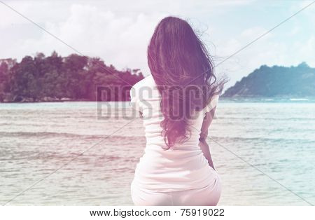 Lonely Woman in White Casual Outfit with Long Black Hair Sitting at Beachfront on a Windy Sunny Day. poster