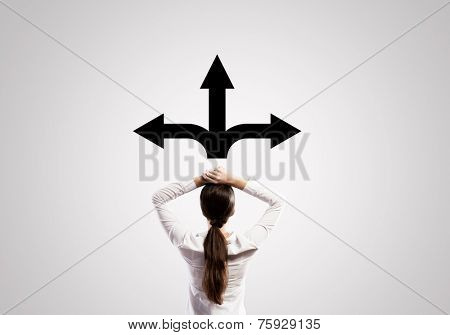 Rear view of thoughtful businesswoman trying to choose direction