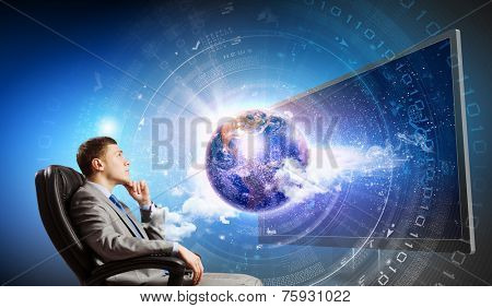 Young businessman sitting in chair behind tv. Elements of this image are furnished by NASA