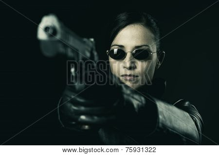 Attractive Female Criminal Pointing A Gun