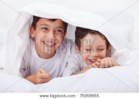 Little boys giggling together - having fun under the quilt