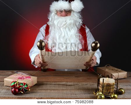 Santa Claus holding his Naughty and Nice list on a scroll of parchment paper. Santa is seated at a wood table with presents and candle, Horizontal format on light to dark red background.