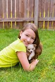 kid girl and puppy dog happy playing with chihuahua pet lying in backyard lawn poster