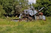 An old rusty self-propelled combine is parked in a pasture with several horses in the background. poster