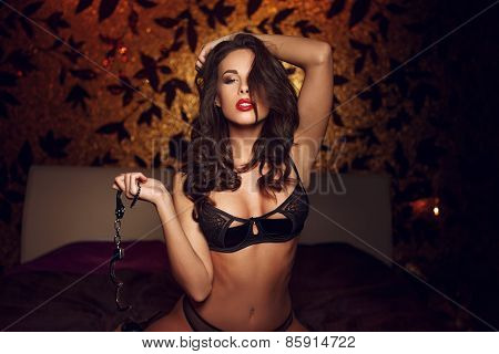 Sexy Woman Kneeling And Holding Handcuffs On Bed