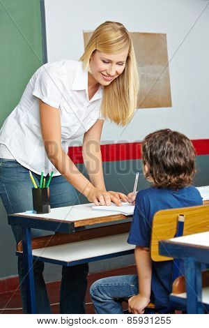 Teacher helping elementary school student in class at his desk
