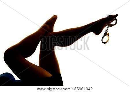 Silhouette Of Woman Legs Kicked Up With Handcuffs On The Toes