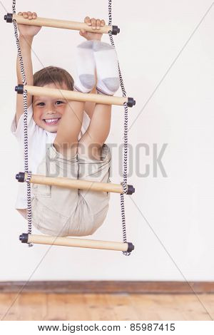 Youth Concept: Happy Laughing Caucasian Little Boy Usiing Sport Equpment Indoors