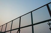 Steel mesh barrier Tennis Court. green steel mesh on sky background poster