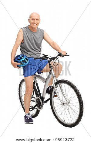 Full length portrait of a senior biker holding a blue helmet seated on his bike and looking at the camera isolated on white background