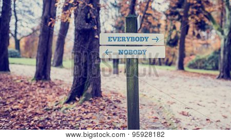 Signpost With Arrows Pointing Two Opposite Directions Towards Everybody And Nobody