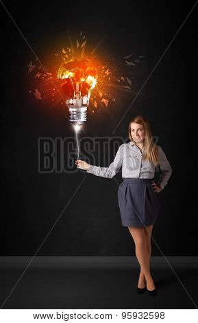 Businesswoman with an explosion bulb on black background