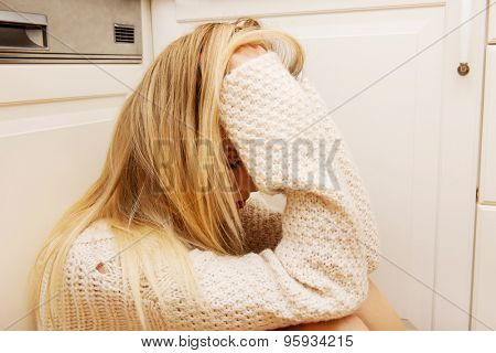 Sad lonely young woman sitting in the kitchen at home.