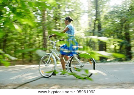 Modern girl riding bicycle in natural environment