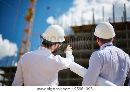 Rear view of architects looking at construction while one of them showing it to colleague
