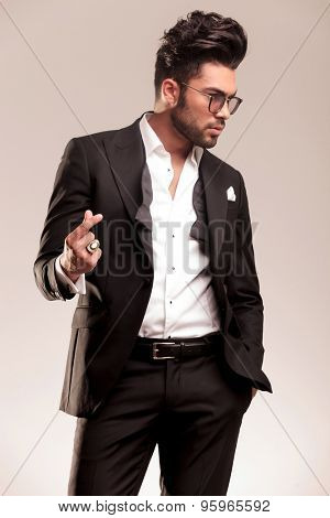 Picture of a attractive young business man snapping his fingers while looking away from the camera.