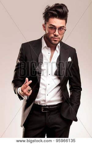 Portrait of a young elegant business man snapping his fingers while looking at the camera.