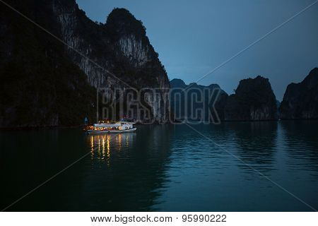 Illuminated boat anchored in the calm Ha Long Bay (UNESCO World Heritage Site) near the limestone mountain.