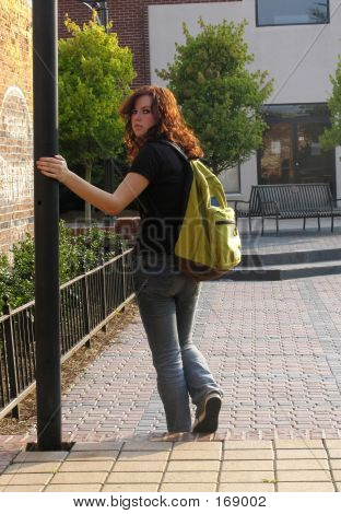 teen girl walking downtown with a bookbag looking back toward camera poster