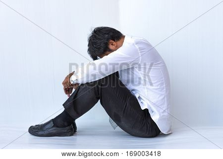 Middle-aged businessman sit hugging his depression after the unemployed on white background.