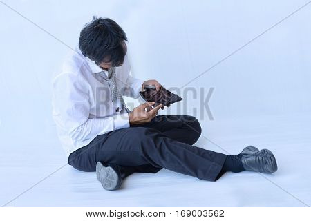 Businessman middle-aged sitting and holding empty wallet has no money on white background.