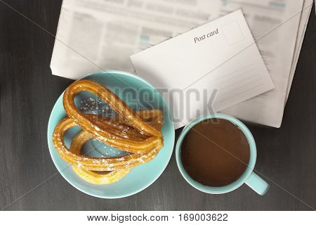 Plate of churros, traditional Spanish, especially Madrid, dessert, particularly for Sunday breakfast, with cup of hot chocolate, blurred newspaper, and blank postcard with copy space