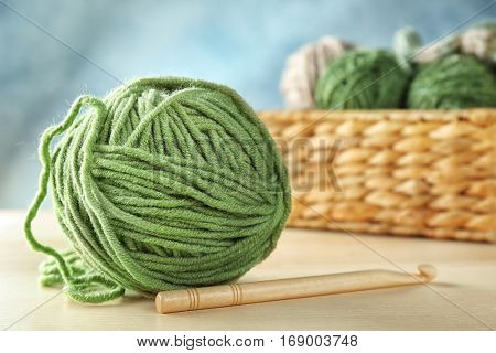Green ball of knitting yarn and hook on wooden table