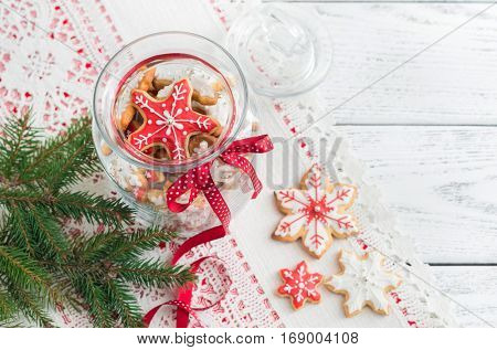 Christmas gingerbread cookies in glass jar on wooden table.