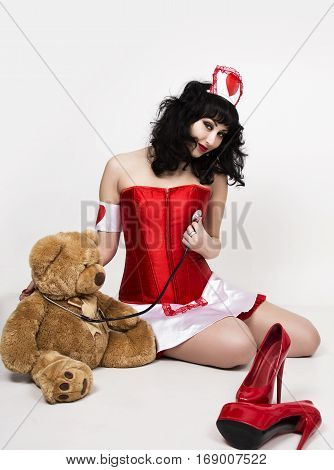 young beautiful woman dressed as nurse, medical carnival costume, she holding a stethoscope and sitting on a floor with teddy bear.