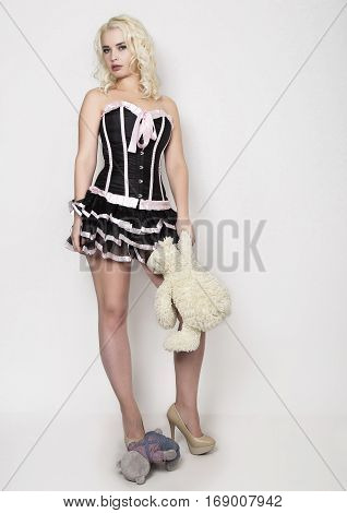 Beautiful young woman dressed as a sexy maid-servant in skimpy uniform, posing.