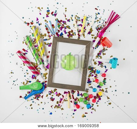Various party confetti balloons noisemakers and decoration on a white background with photo frame and a balloon with a smile. Colorful celebration background. Top view. Flat lay