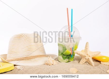 Refreshing cocktail straw hat beach slippers suntan lotion and starfish on the sand on a white background