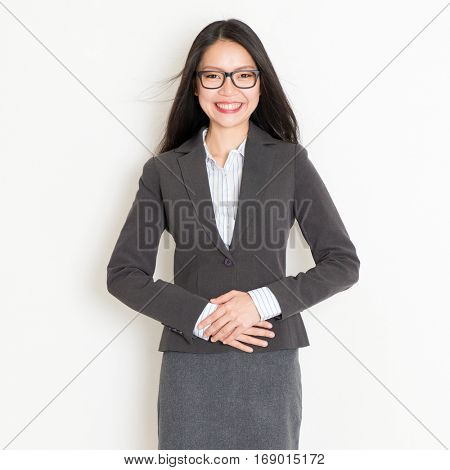 Portrait of young Asian businesspeople in formalwear smiling and looking at camera, standing on plain background.