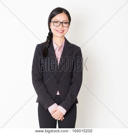 Portrait of Asian business people in formalwear smiling and looking at camera, standing on plain background.