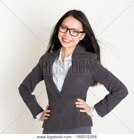 Portrait of young Asian business woman in formalwear smiling and looking at camera, standing on plain background.