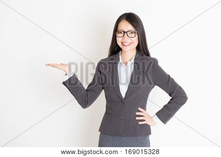 Portrait of Asian businesswoman in formalwear smiling and hand holding something, standing on plain background.