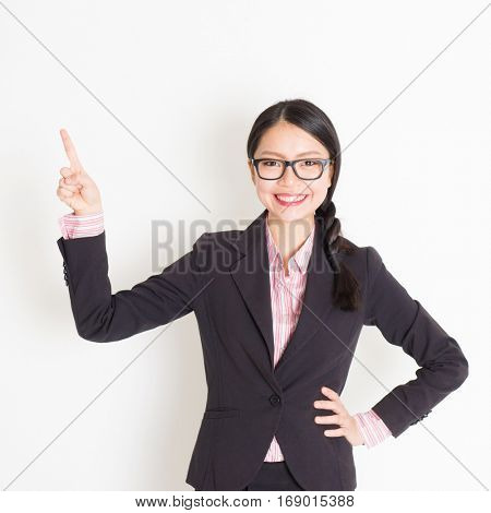 Portrait of Asian businesswoman in formalwear smiling and finger pointing on something, standing on plain background.