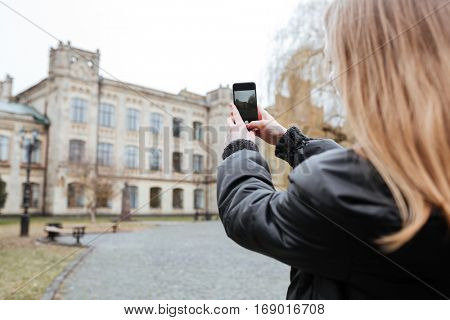 Back view of a young woman taking photo of a beautiful building with mobile phone